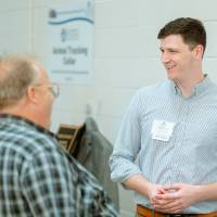 An engineering student speaking with guests at the Engineering Design Project Preview